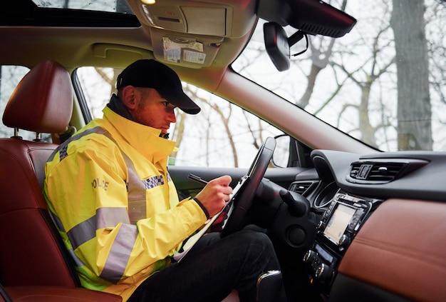 녹색 제복을 입은 남성 경찰관은 자동차에 앉아서 문서 작업을 합니다.