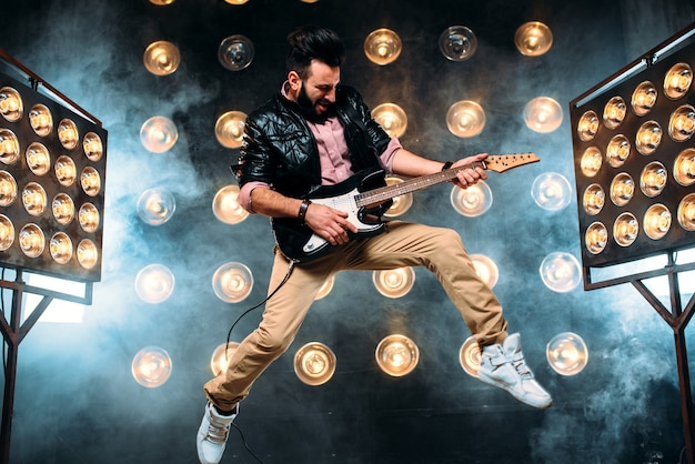 Male pop star with electro guitar on the stage with the decorations of lights.