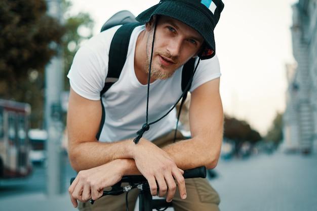 La tenuta maschio del ritratto ha attraversato le mani sul manubrio della bicicletta.