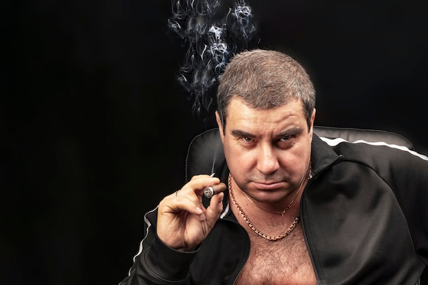 Male portrait, a man smoking a cigar. experienced criminal smoking a cigar sitting on a chair.