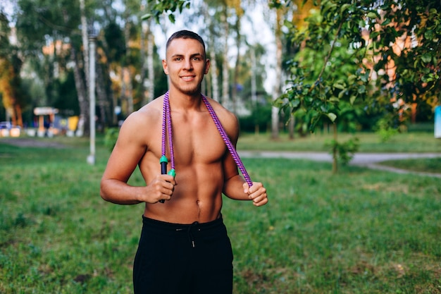 Male portrait standing with jump rope on the lawn outdoor