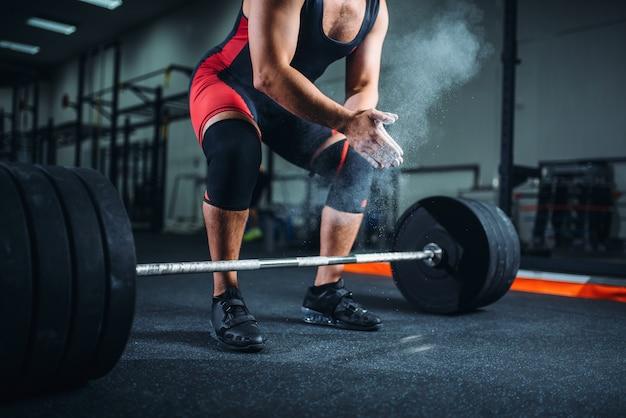 Пауэрлифтер мужского пола в спортивной одежде трет руки тальком, подготовка к упражнениям со штангой в тренажерном зале.