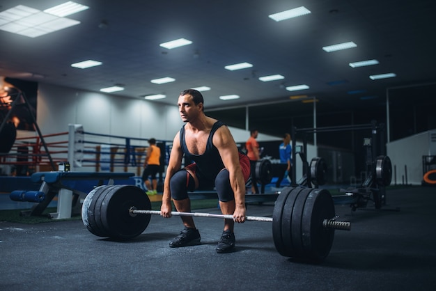 Male powerlifter starting deadlift a barbell in gym.