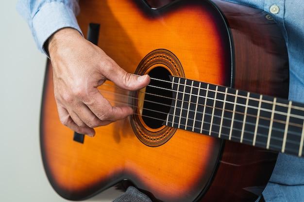 彼の居間でアコースティックギターで練習している男性