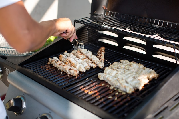 Male prepares barbecue outdoors