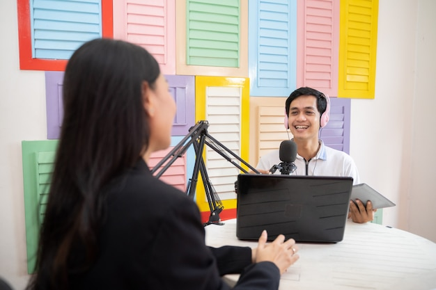 A male presenter chats with a woman using a microphone during a podcast