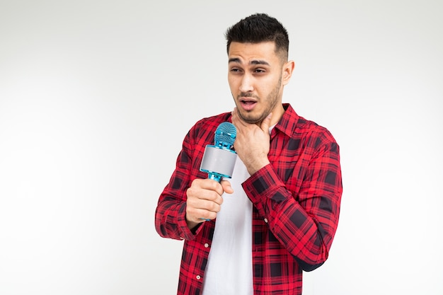 Male presenter with a microphone in his hands has a sore throat on a white isolated studio background.