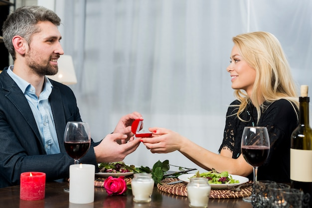 Male presenting gift box with ring to blond female at table with dishes and bloom