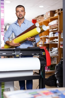 Male printing worker with rolls of colored paper