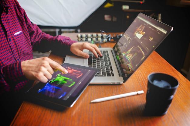 Мужской продюсер редактирует видео на своем ноутбуке в студии
