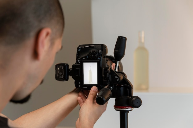Фотограф продукта мужского пола делает свою работу в студии