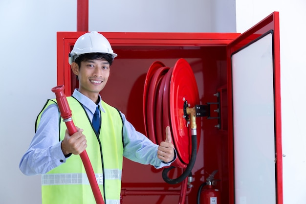 Male professional checking a fire extinguisher.