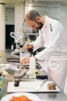 Мужской профессиональный шеф-повар готовит на кухне.