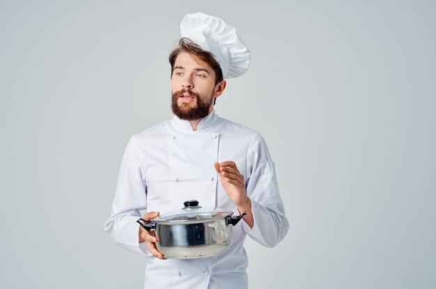 フードレストランを準備する彼の手に鍋を持つ男性のプロのシェフ