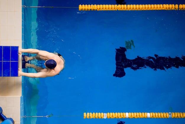 Мужской профессиональный пловец в бассейне, вид сверху.