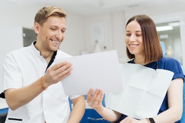 手袋とマスクを持った男性のプロの歯科医が紙の写真を持って、患者の歯の治療がどのように見えるかを示します