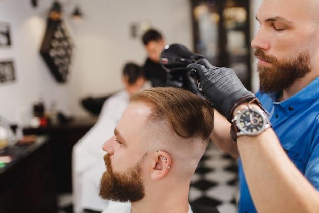 남성 전문 미용사 서빙 클라이언트, 헤어 드라이기로 머리카락을 건조
