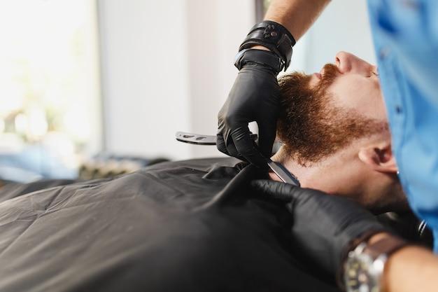 남성 전문 미용사 서빙 클라이언트, 면도 두꺼운 큰 수염 면도칼