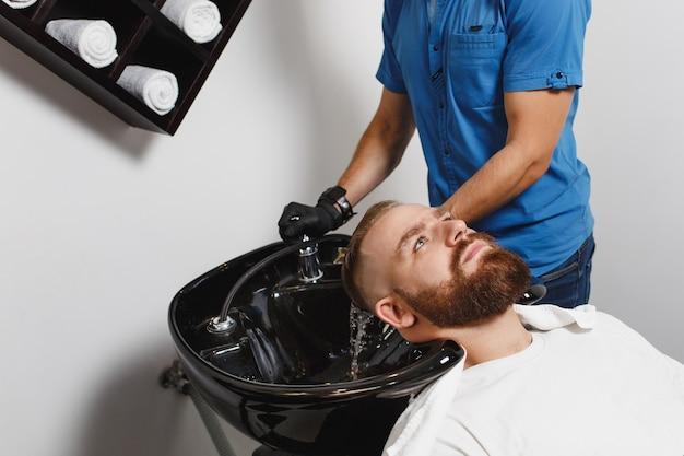 남성 전문 미용사, 수건으로 닦아 검은 유행 세면대에 머리를 씻는 클라이언트를 제공