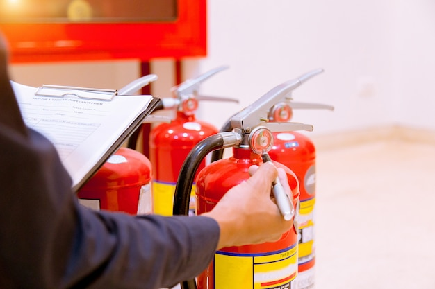 Male professional inspection fire extinguisher, safety concept.