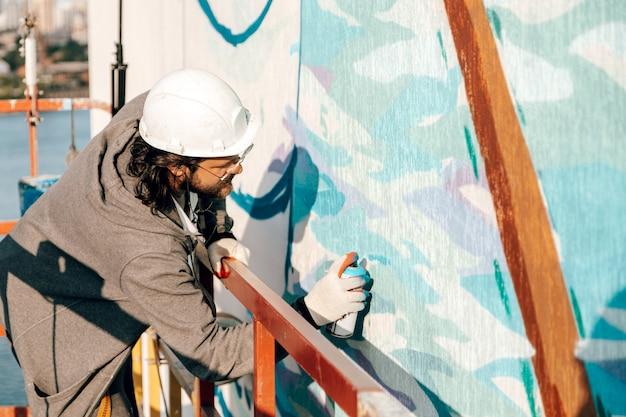 Мужской профессиональный маляр-строитель рисует стену нового здания на большой высоте