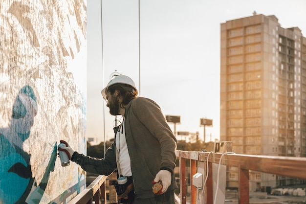 Male professional painter builder paints the wall of a new building at high altitude