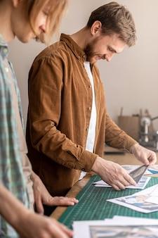 Мужчина-профессионал кожевник смотрит фотографии бумажные фото примеры работы из кожи ручной работы