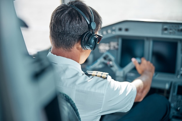 Male professional in uniform and headphones is holding rudder at control while driving jet at work