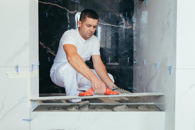 Мужчина-профессиональный работник монтирует керамическую плитку в ванной комнате