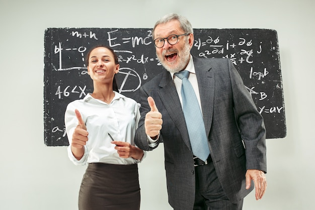 教室で黒板に対して男性教授と若い女性