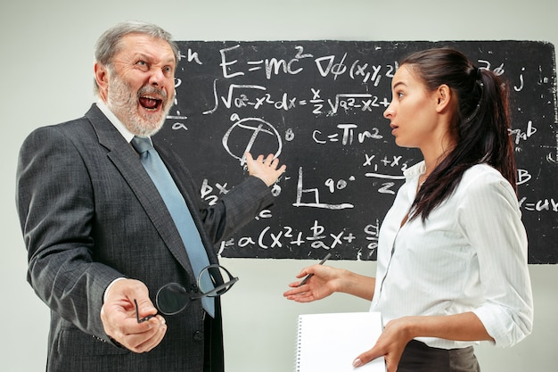 Male professor and young woman against chalkboard in classroom