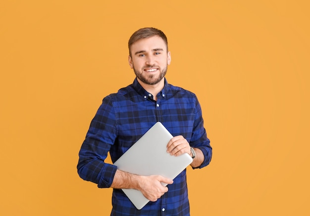 Программист-мужчина с ноутбуком на цветном фоне