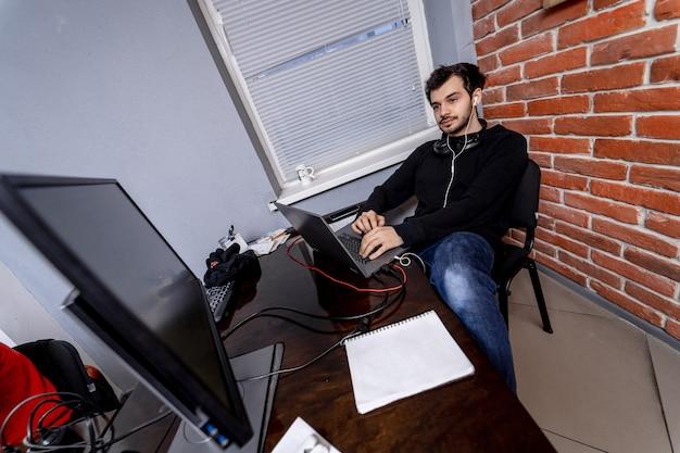 オフィスでモニターの近くのデスクトップコンピューターで作業している男性プログラマー