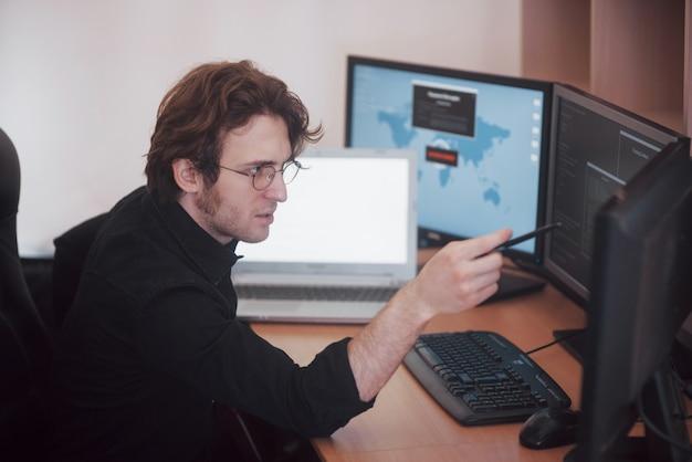 Мужской программист работает на настольном компьютере со многими мониторами в офисе в разработке программного обеспечения компании. дизайн сайтов, программирование и технологии кодирования