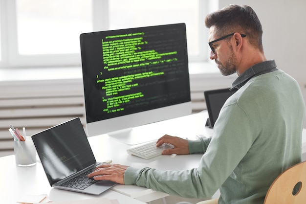 ソフトウェア開発会社のオフィスで多くのモニターを備えたデスクトップコンピューターで作業している男性プログラマー
