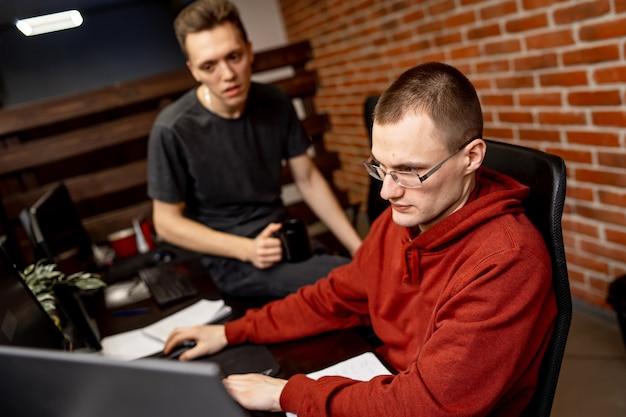 Программисты-мужчины, работающие на настольном компьютере возле монитора в офисе компании по разработке программного обеспечения. технологии программирования и кодирования веб-сайтов.
