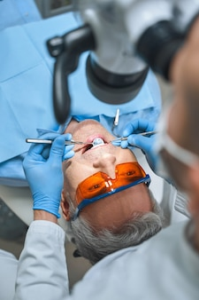 Male in protective glasses is lying in dental chair while specialist is examining him with tools