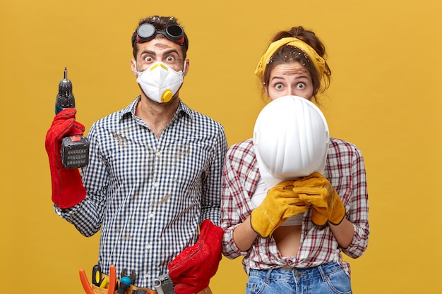 Male in protective mask standing with drill and female hiding under white hardhat renewing their flat working together using building instruments. construction workers improving something in room