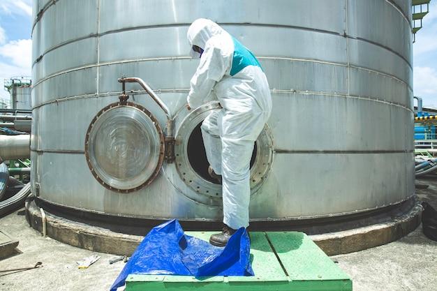 맨홀 연료 스테인리스 탱크 화학 보호 구역 밀폐 공간 위험에 남성 보호복 작업자 프리미엄 사진