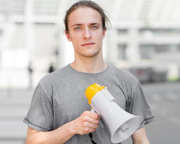 Мужчина протестующий держит мегафон