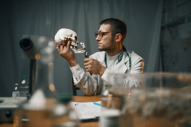 실험실 코트를 입은 남성 정신과 의사가 인간의 두개골, 정신 병원을 검사합니다. 정신 질환을위한 클리닉의 의사