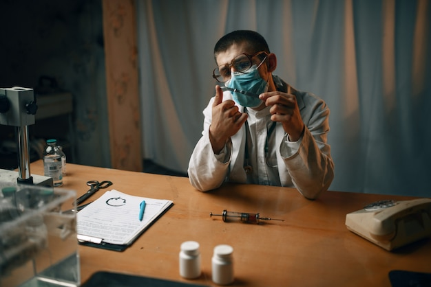 Мужской психиатр в маске и очках сидит за столом в психбольнице. врач в клинике для душевнобольных