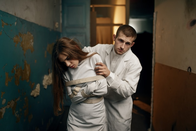 Male psychiatrist leads crazy female patient in straitjacket, mental hospital. woman in strait jacket undergoing treatment in clinic for the mentally ill