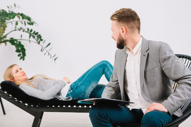 Male psychologist looking at her female patient lying on couch
