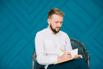 Male psychologist sitting on chair writing on diary with pencil against blue wallpaper