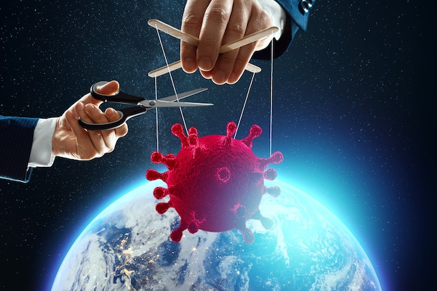 Male puppeteer hand thread coronavirus on the background of the earth. the concept of shadow government, world conspiracy, manipulation, control.