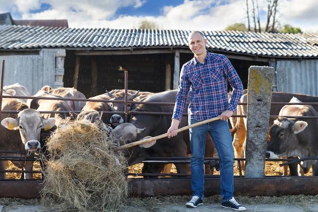 Мужчина-владелец ранчо на ферме с крупным рогатым скотом на заднем плане
