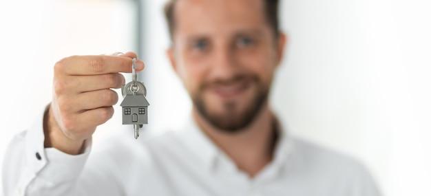 男性の不動産業者またはブローカーは、新しい家やアパートのショーキーを保持しています。家賃のコンセプト