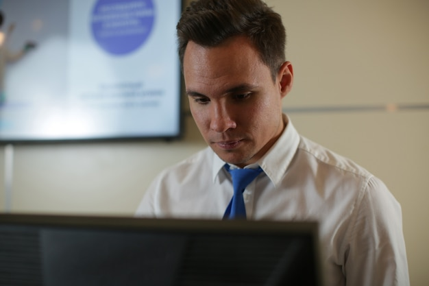 A male receptionist stands behind the reception at the hotel. check-in guest. booking rooms.