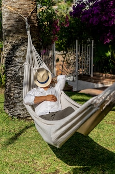 Male relaxing in a hammock in the garden.
